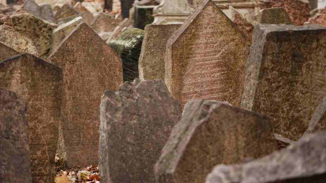 Old weathered headstones with inscriptions in cemetery