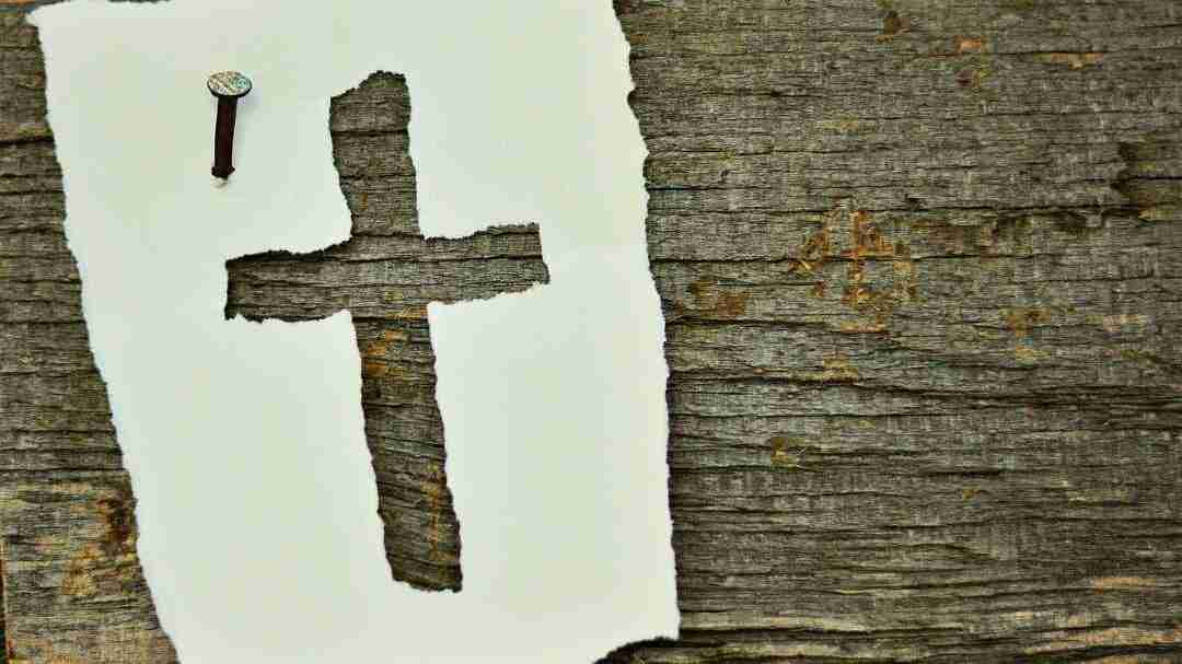 Cross cut into a piece of paper and nailed onto wood